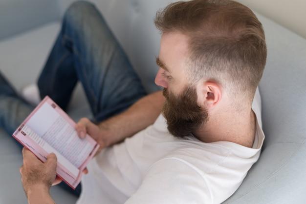 Concentrado homem focado no conteúdo do livro sentado no sofá Foto gratuita