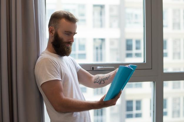 Concentrado jovem com livro de leitura de tatuagem Foto gratuita