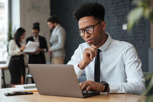 Concentrado jovem empresário africano Foto gratuita