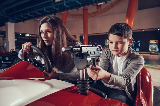 Concentrado mãe e filho dirigindo o carro de brinquedo no shopping Foto Premium