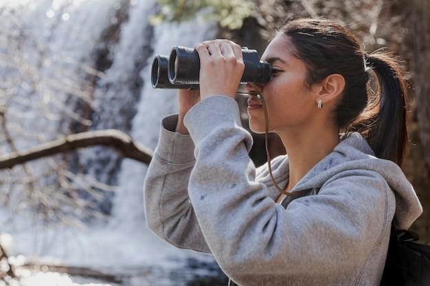 Concentrado, morena, mulher, usando, binóculos Foto gratuita