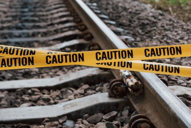 Concepção de terrorismo. explosivo perigoso deitado na ferrovia. fita isolante amarela na frente Foto gratuita