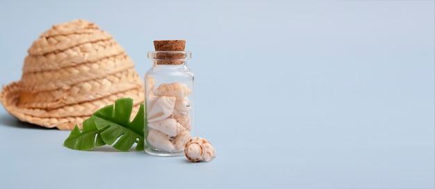 Conchas do mar em uma mini garrafa, folhas tropicais, chapéu de palha. o conceito de mar, férias, viagens Foto Premium