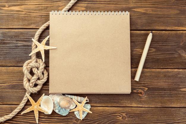 Conchas e bloco de notas na mesa de madeira, vista superior com espaço de cópia Foto Premium