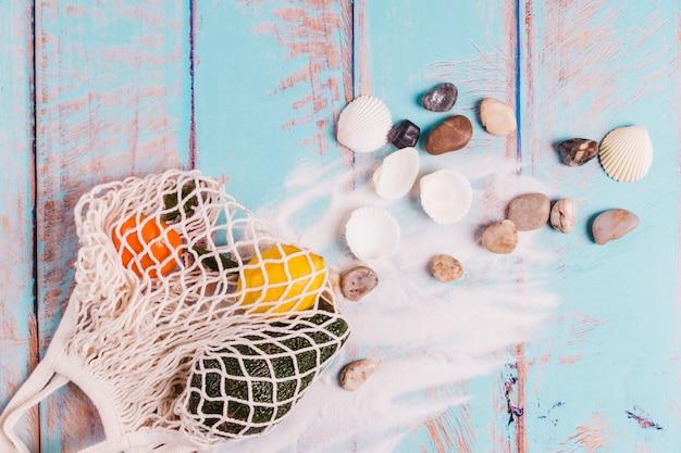 Conchas pedras areia e frutas na placa de madeira Foto gratuita