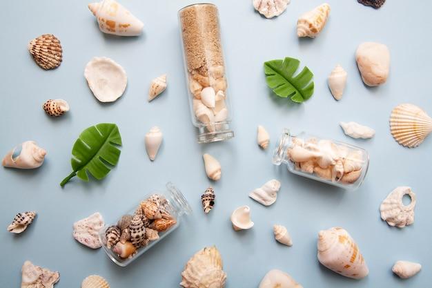 Conchas planas leigos, mini garrafas, folhas tropicais, chapéu de palha. o conceito de mar, férias, viagens Foto Premium