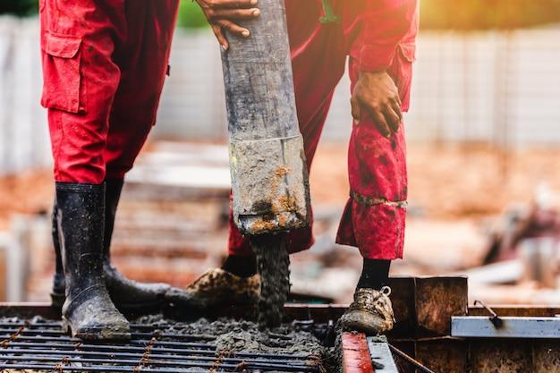 Concreto do crescimento do controle do trabalhador dos homens da construção Foto Premium