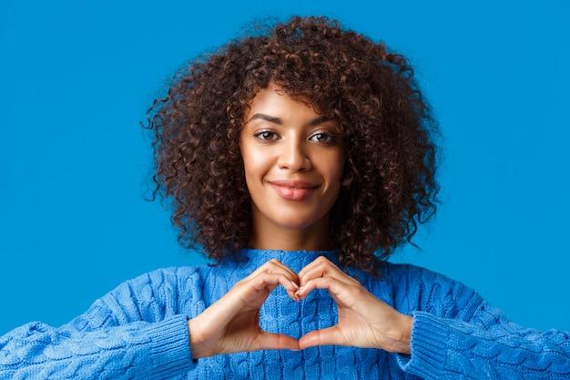 Concurso de retrato de close-up e bonita mulher romântica afro-americana expressar seus sentimentos com gesto, mostrando sinal de coração e sorrindo, ter simpatia, confessar sobre azul Foto Premium