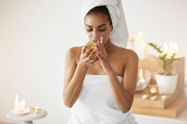 Concurso mulher africana com toalha na cabeça bebendo chá descansando no salão spa. Foto gratuita