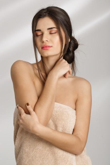 Concurso mulher desfrutando de pele macia após o tratamento de spa após preceder. Foto gratuita
