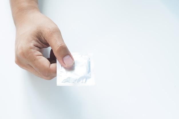 Condom na mão masculina no fundo branco Foto gratuita
