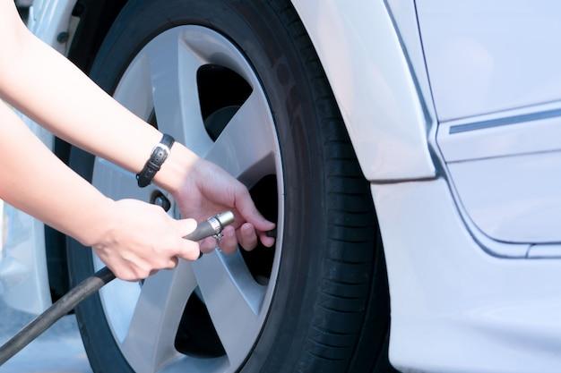 Condutor de enchimento de ar em um pneu de carro, inflação do pneu Foto Premium