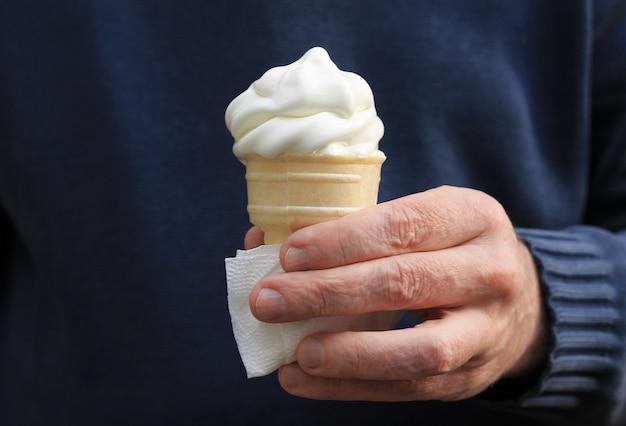Cone de gelado branco que derrete na mão de um homem, mão em uma camisola longa da luva. Foto Premium