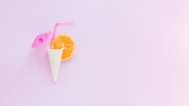 Cone de waffle com laranja, palha e guarda-chuva Foto gratuita