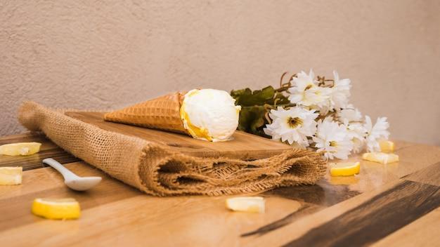 Cone de waffle com sorvete perto de fatias de frutas frescas e flores no guardanapo Foto gratuita