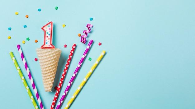 Cone de waffle com vela número um; serpentina e bebendo palhas em fundo azul Foto gratuita