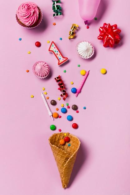 Cone de waffle derramado de gemas; granulados; velas flâmulas; balão; gemas e aalaw em fundo rosa Foto gratuita
