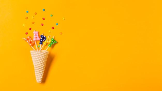 Cone de waffle no texto feliz velas com granulado no pano de fundo amarelo Foto gratuita
