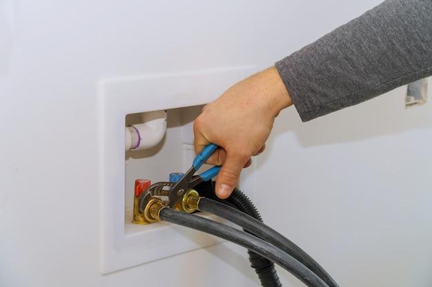 Conectar a mangueira de abastecimento de água à máquina de lavar roupa usando a chave Foto Premium