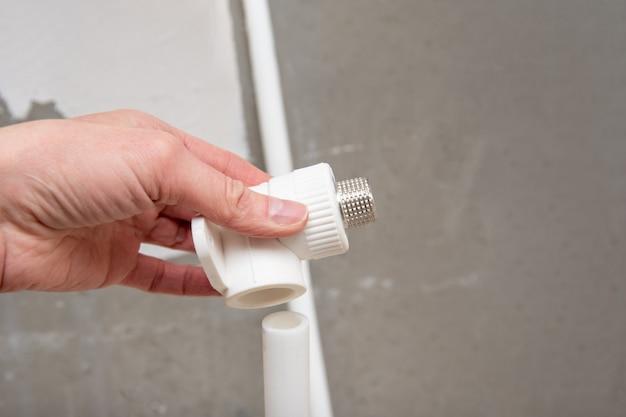 Conector de tubos de encanamento na mão. encaixe de tubo roscado macho Foto Premium