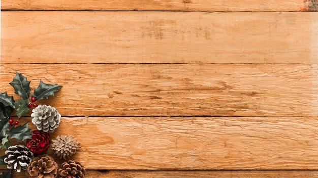 Cones com ramo de azevinho na mesa Foto gratuita