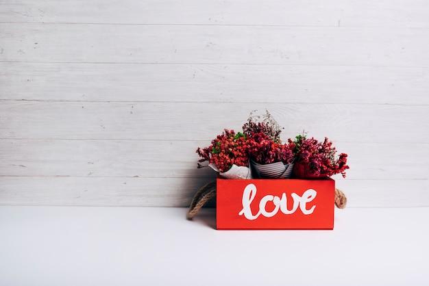 Cones de flores na caixa de amor na mesa branca contra o pano de fundo de madeira Foto gratuita