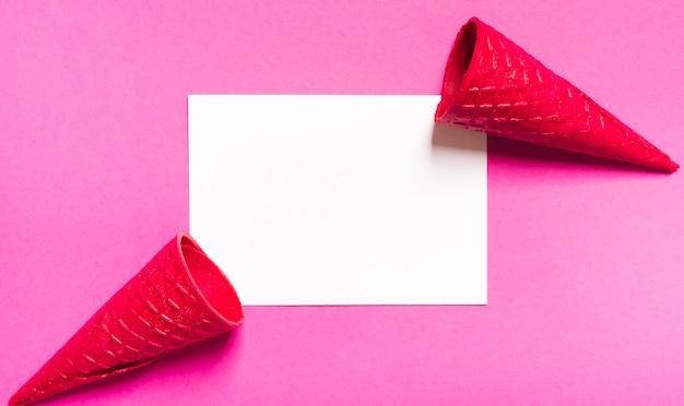 Cones de sorvete crocante e folha branca em fundo rosa Foto gratuita