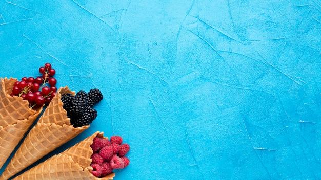 Cones de sorvete plana-leigos com bagas com espaço de cópia Foto gratuita