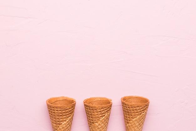Cones de waffle no fundo rosa Foto gratuita