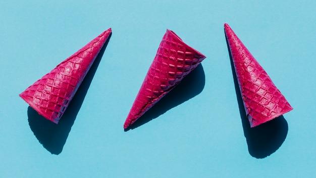 Cones de waffle rosa brilhante na superfície azul Foto gratuita