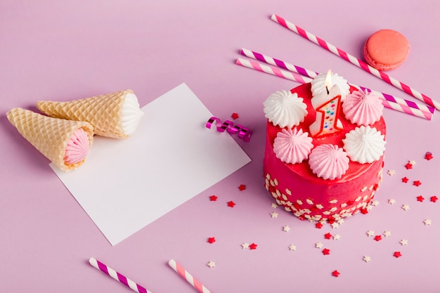 Cones do waffle no papel perto do bolo delicioso com chuviscos e palhas bebendo no contexto roxo Foto gratuita