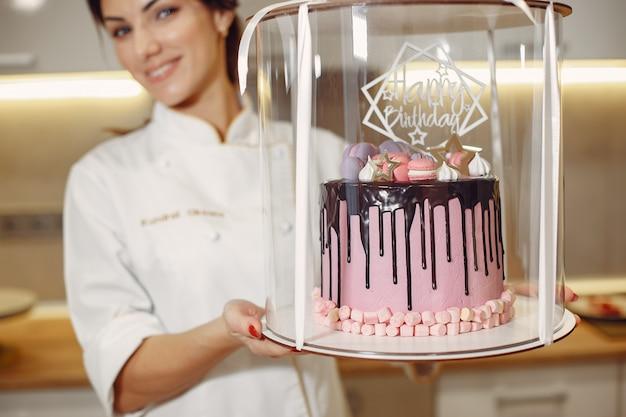 Confeiteiro de uniforme decora o bolo Foto gratuita