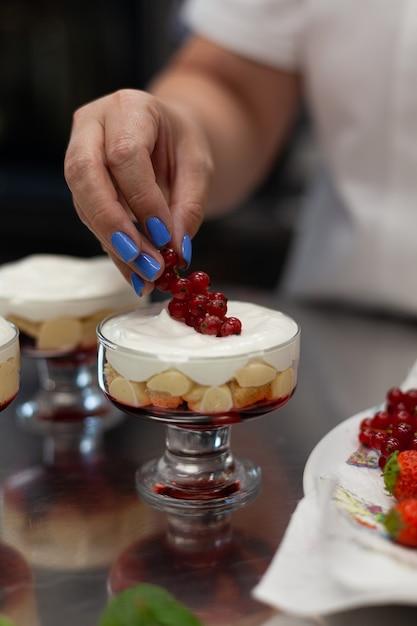 Confeiteiro decora sobremesa com frutas vermelhas Foto Premium