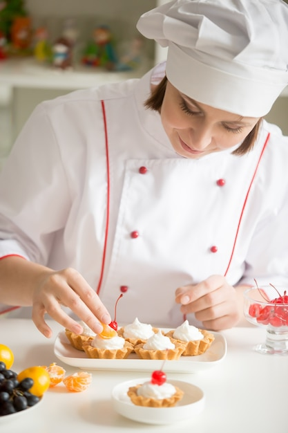 Confeitera feminina profissional que decora mini tartes de frutas Foto gratuita