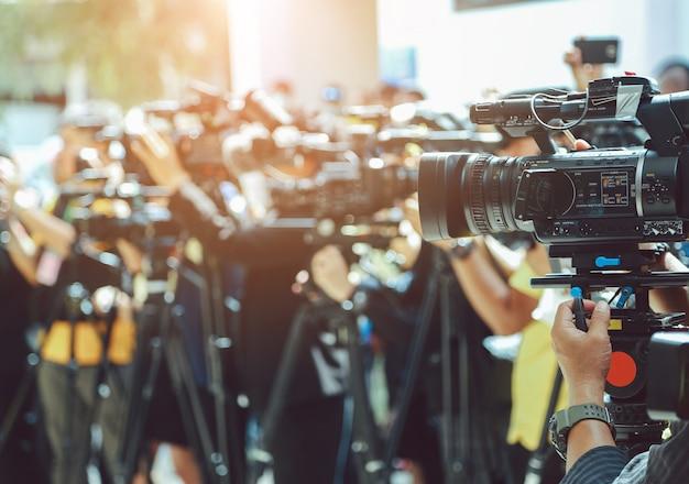Conferência de imprensa. câmera de vídeo no grupo borrada de imprensa e mídia fotógrafo Foto Premium