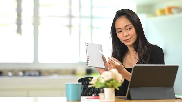 Conferência de jovem empresária asiática de colegas através de um tablet. Foto Premium