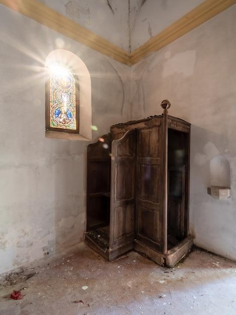 Confessionário de uma igreja abandonada com o sol entrando pela janela colorida Foto Premium