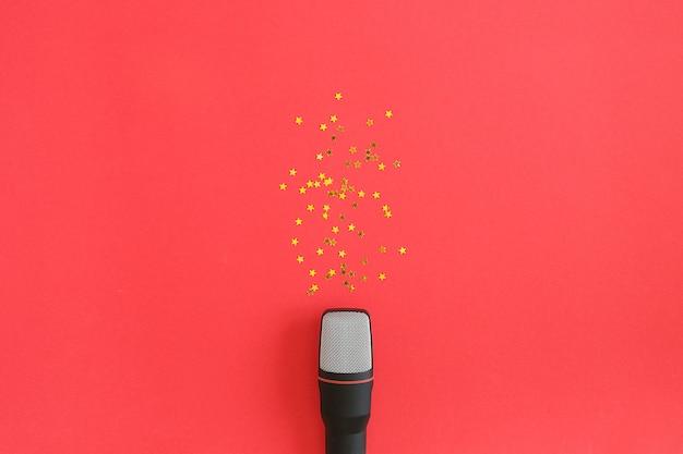 Confete de estrelas pretas de microfone e ouro sobre fundo vermelho. festa de música conceito ou karaokê. Foto Premium