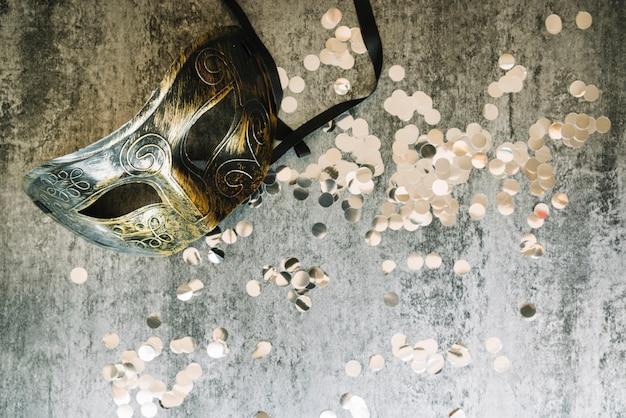 Confete e máscara em fundo cinza Foto gratuita