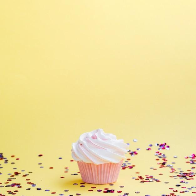 Confete e muffin de aniversário simples Foto gratuita