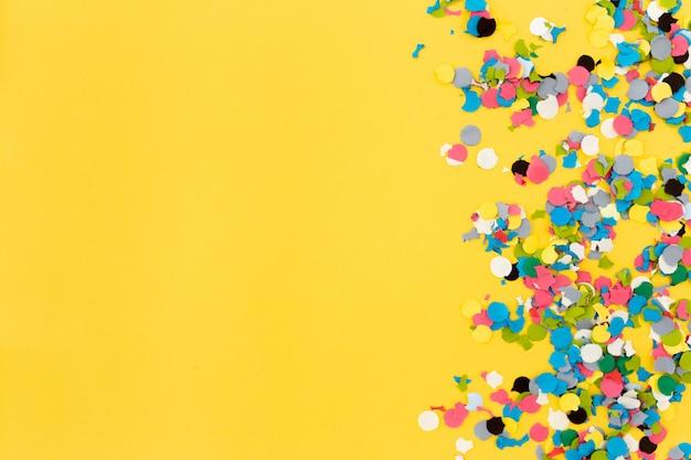 Confete em fundo amarelo Foto gratuita