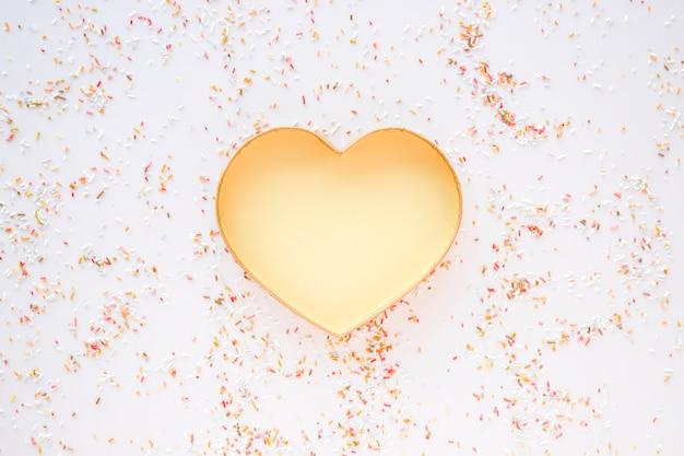 Confete em torno do coração de ouro Foto gratuita