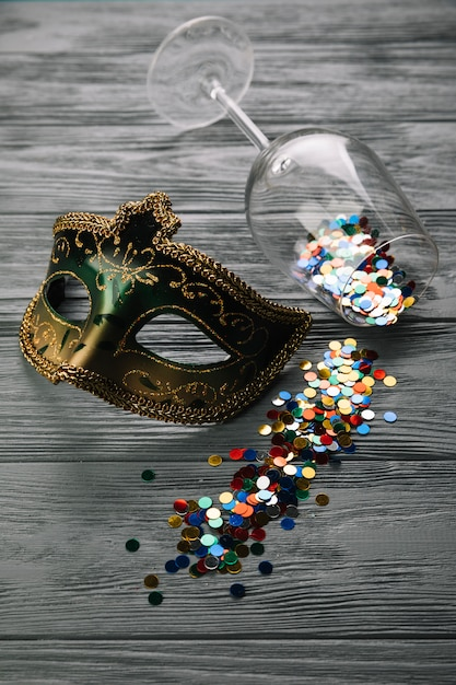 Confetes coloridos caídos do copo de vinho com máscara de penas de carnaval de máscaras na mesa de madeira Foto gratuita