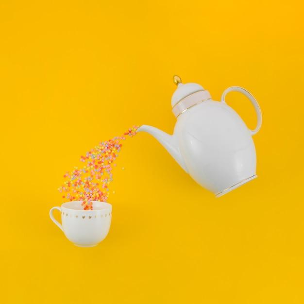 Confetes coloridos derramando de bule de chá branco no copo cerâmico contra fundo amarelo Foto gratuita