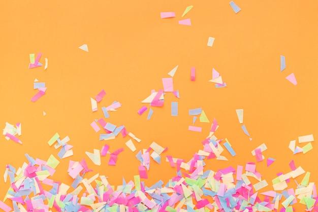 Confetes coloridos em um fundo laranja Foto gratuita