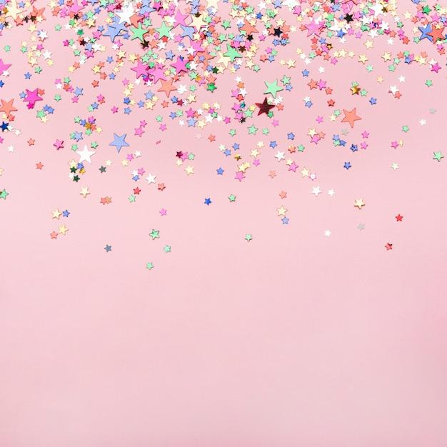 Confetes de estrelas coloridas em fundo rosa com espaço de cópia Foto gratuita