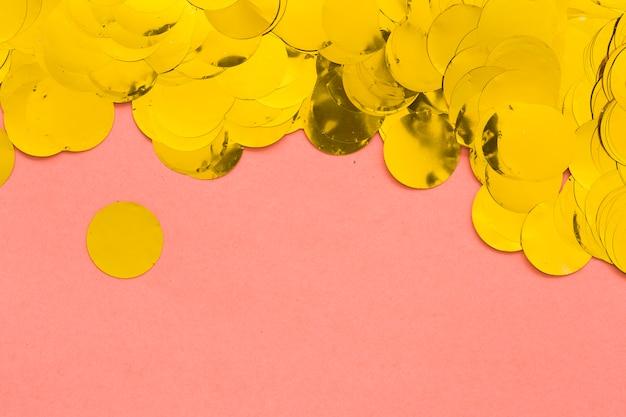 Confetti dourado em rosa Foto gratuita