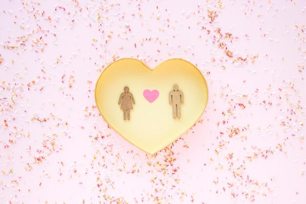 Confetti em torno do coração com casal heterossexual Foto gratuita