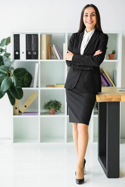 Confiante jovem empresária permanente no escritório com os braços cruzados Foto gratuita