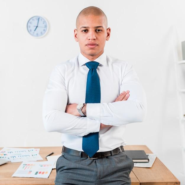 Confiante jovem empresário em frente a mesa de madeira com o braço cruzado Foto gratuita